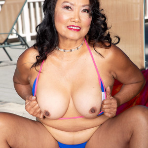 Sixty Plus Oriental MILF Mandy Thai removes a wire swimsuit to get nude by a pool