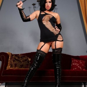 Stunning dark-haired Belle Noir slaps her inviting booty with a flog in a revealing ebony dress