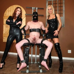 Fully-clothed dolls Zoey and Kendra deny a hooded masculine slave from having an ejaculation