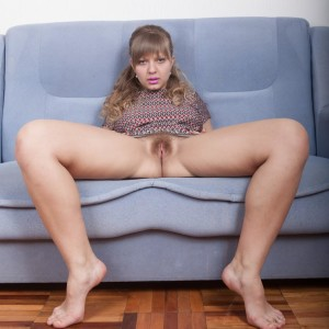 Sandy-haired first timer Jamaica finger spreads her bush during a nude solo shoot on a sofa
