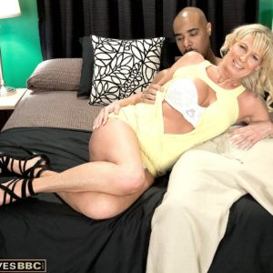 Blonde grandma Nikki Chevious works on seducing a black boy in a yellow sundress