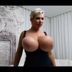 Blonde solo model Claudia Marie sucks on a nip after unleashing her massive tits