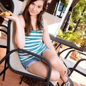 Brunette nubile Kasey Warner tongues a banana before loosing her teenie tits outdoors