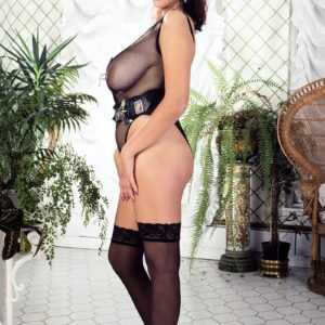 Elderly MILF porno starlet Jeannine Oldfield tongues the nipples of her immense boobies in semitransparent lingerie