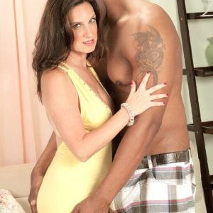 Old lady Gillian Sloan demonstrates her bald snatch on the lap of young ebony dude