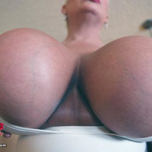 Platinum ash-blonde dame Claudia Marie holds her enormous boobies while sucking on a nip