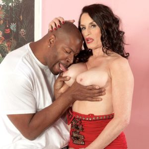 Stellar black-haired grandmother Rita Daniels seduces a younger black guy with her superb legs