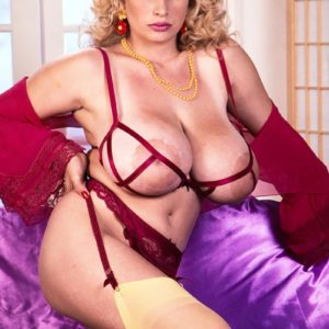 Well known adult film star Crystal Topps lets out her big tits in stockings and garters