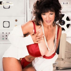 Black-haired businesswoman Buxom BriAnna showcases her great legs and enormous titties at once