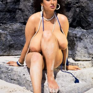 Brown-haired MILF Lisa Phillips touts her hefty breasts and butt on a sandy beach