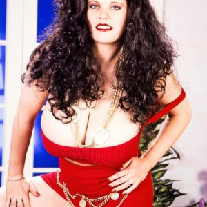 Dark haired chick Cathy Patrick holds her gigantic tits after unsheathing them from a crimson dress