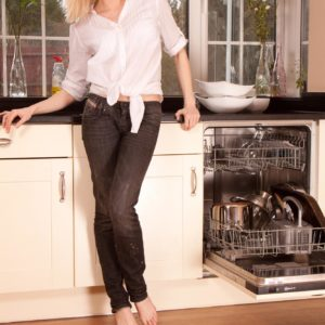 Beguiling experienced dame revealing her sweet ass and unshaven cunt while doing away with denim jeans in a kitchen