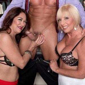 Mature nymphs Renee Black and Scarlet Andrews take turns sucking a rock-hard penis