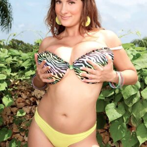 Solo model Valory Irene poses in an outdoor garden setting in a brassiere and g-string