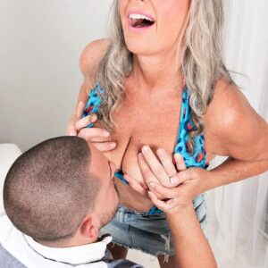 Marvelous sixty plus MILF Silva Foxx seduces a younger dude by flashing her tits in a denim microskirt