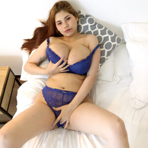 ginger-haired Latina chickj Lucy Rodriguez plays with her giant boobs while getting naked on a bed