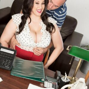 Dark haired BBW pornographic star Angel DeLuca unveiling her enormous tits in an office setting
