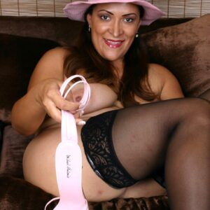 Big-boobed elder woman in a sun hat sheds high-heels from her nylon attired feet