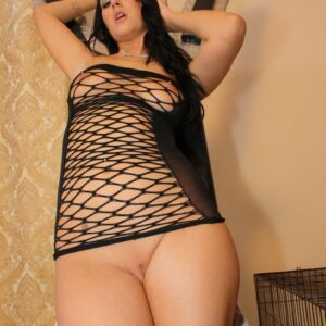 Black-haired Domme Ashley modeling in a dungeon while wearing fetish garments